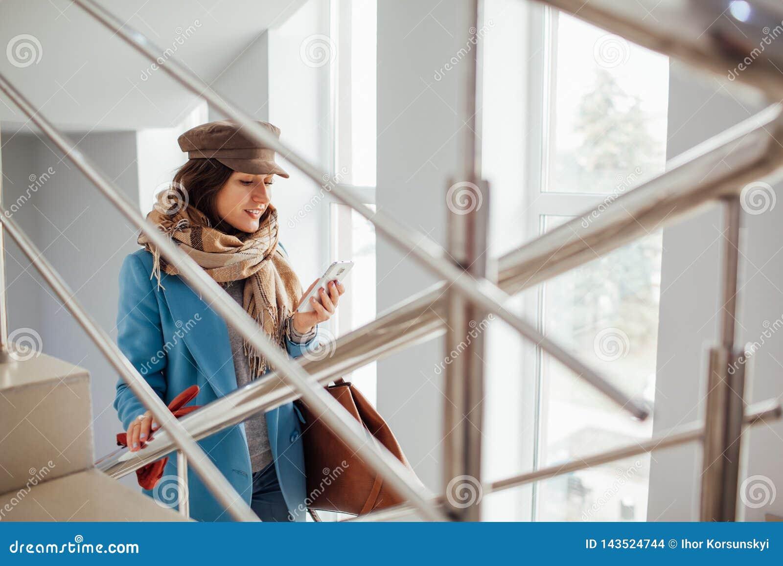 A mulher de negócio no revestimento aumenta as escadas na alameda Compras Forma