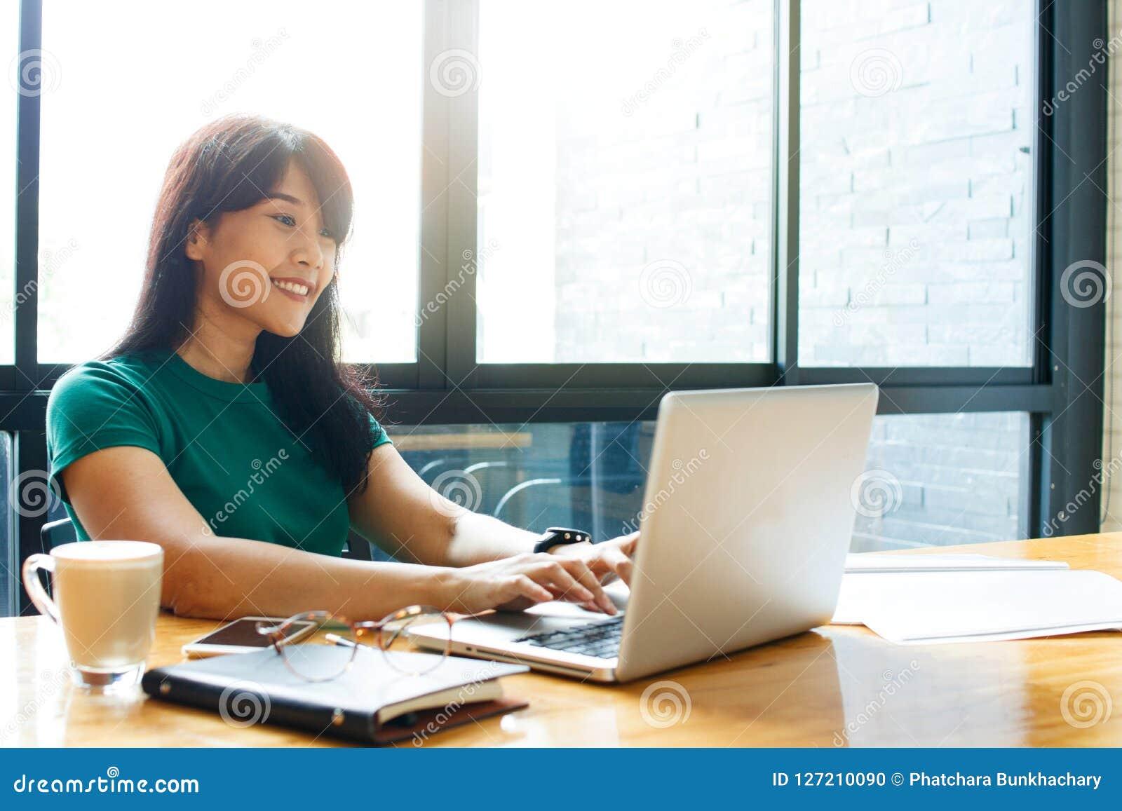 Mulher de negócio nova asiática do proprietário que trabalha em linha, verificando o correio no processo de trabalho de organizaç