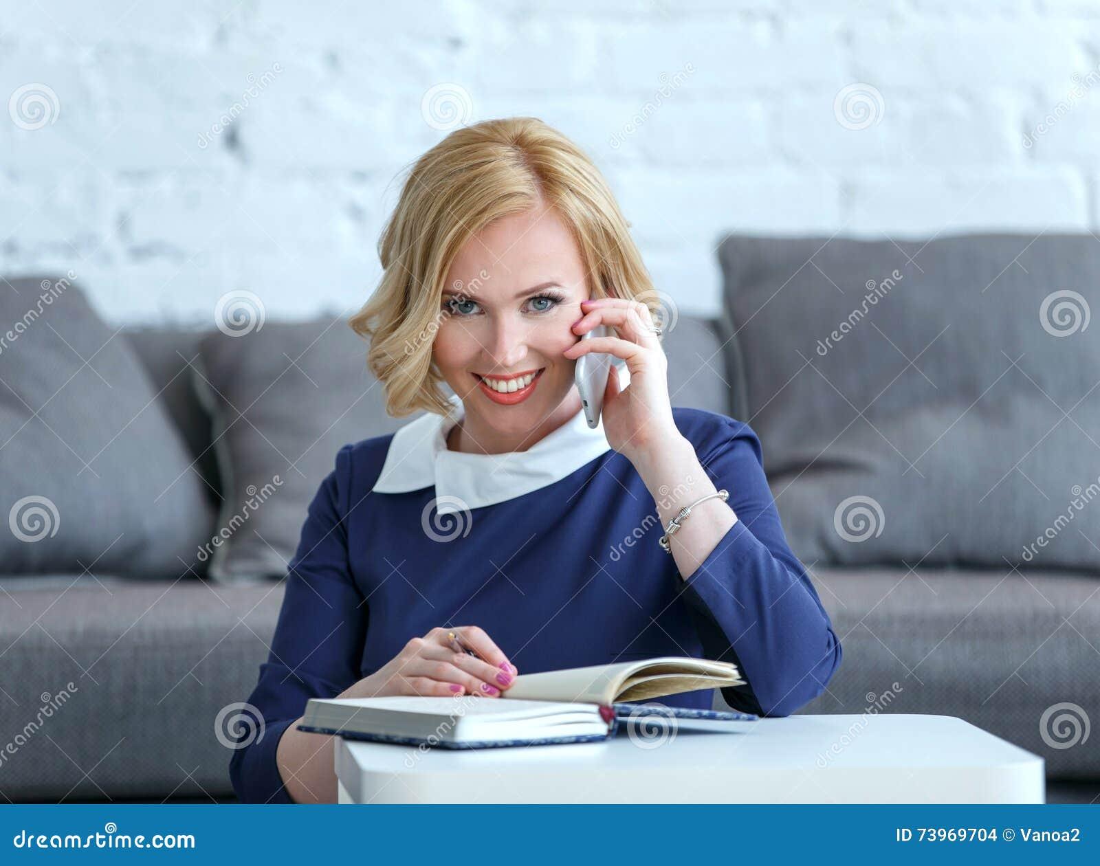 Mulher de negócio nova de sorriso que fala ao telefone celular