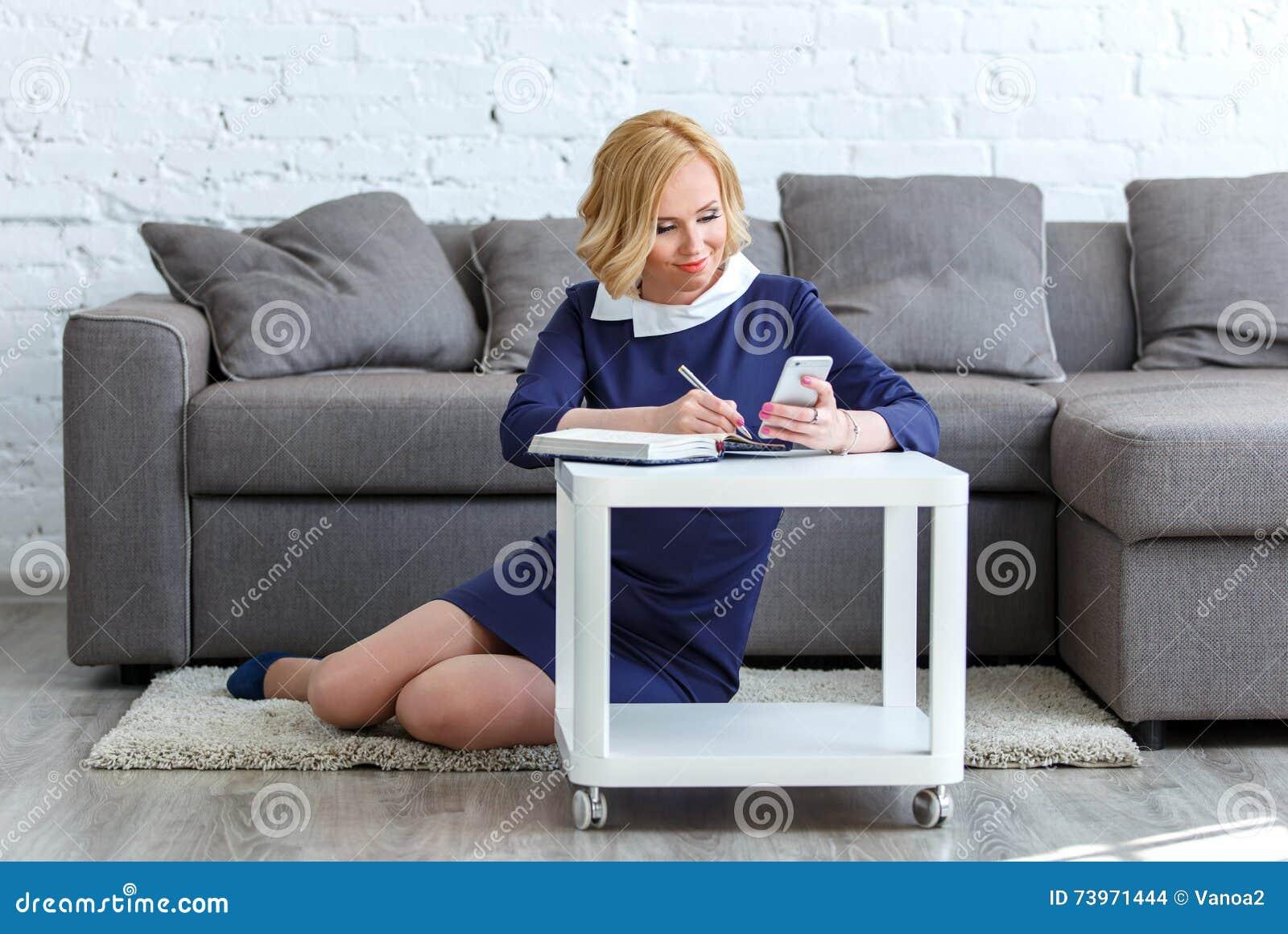 Mulher de negócio nova de sorriso que olha em na seu telefone e escrita