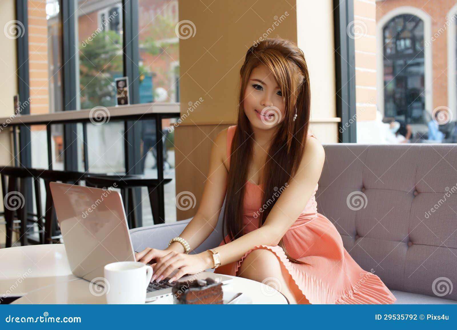 Mulher de negócio nova que senta-se no café com seu portátil