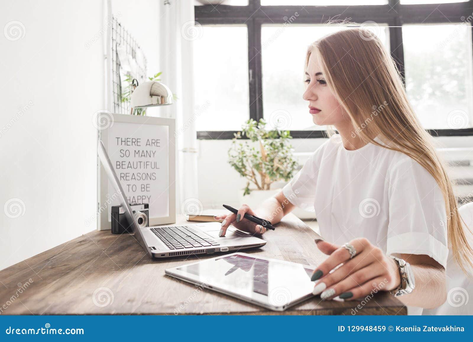 Mulher de negócio nova que trabalha em casa atrás de um portátil e de uma tabuleta Espaço de trabalho escandinavo criativo do est