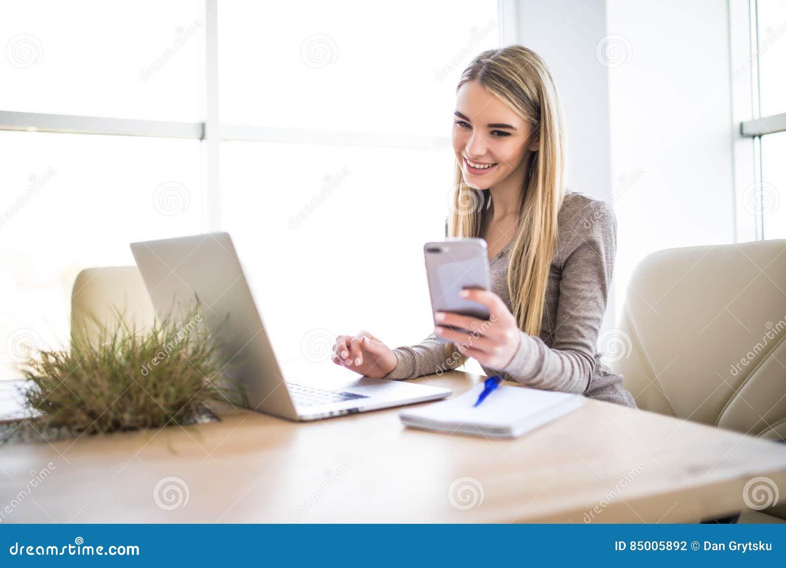 Mulher de negócio nova que usa o telefone à disposição com o portátil no escritório