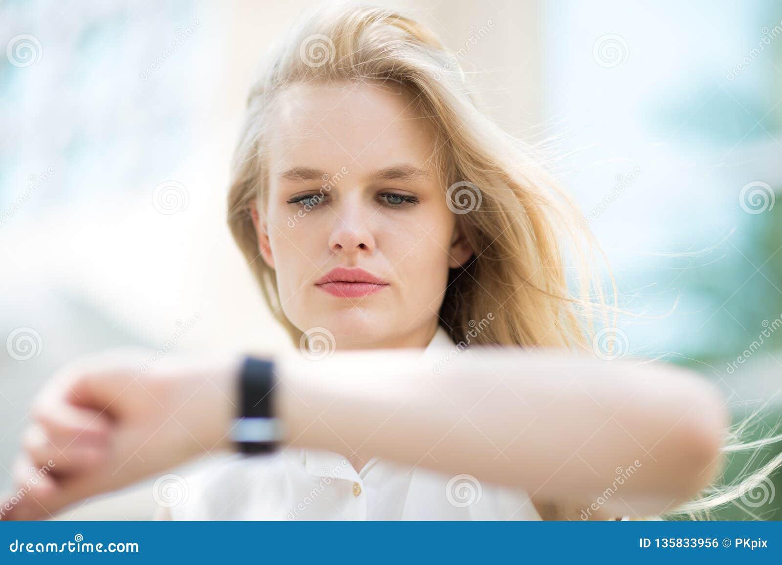 Mulher de negócio nova que verifica o tempo em seu relógio