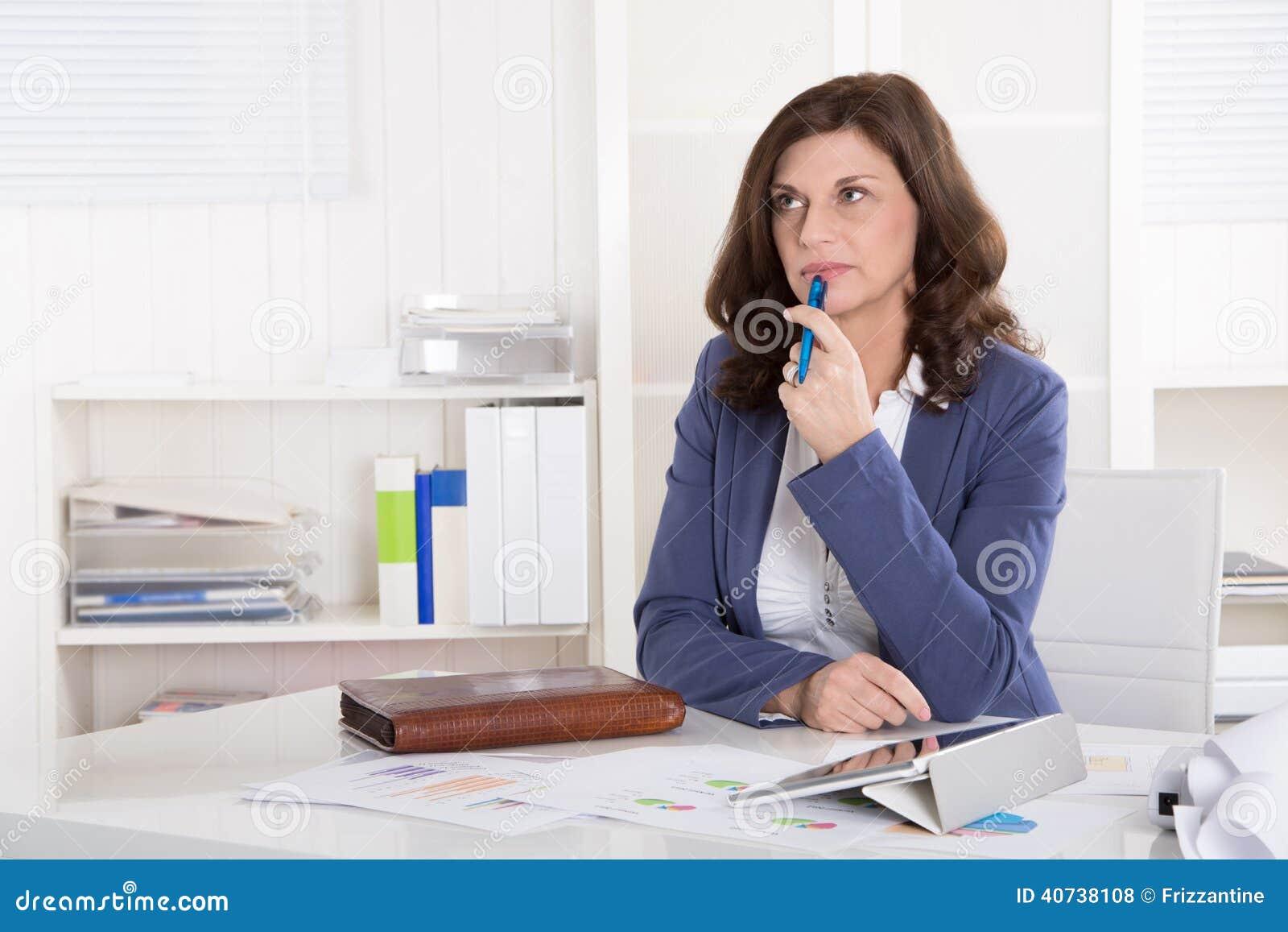 Mulher de negócio pensativa mais idosa infeliz que senta-se na mesa