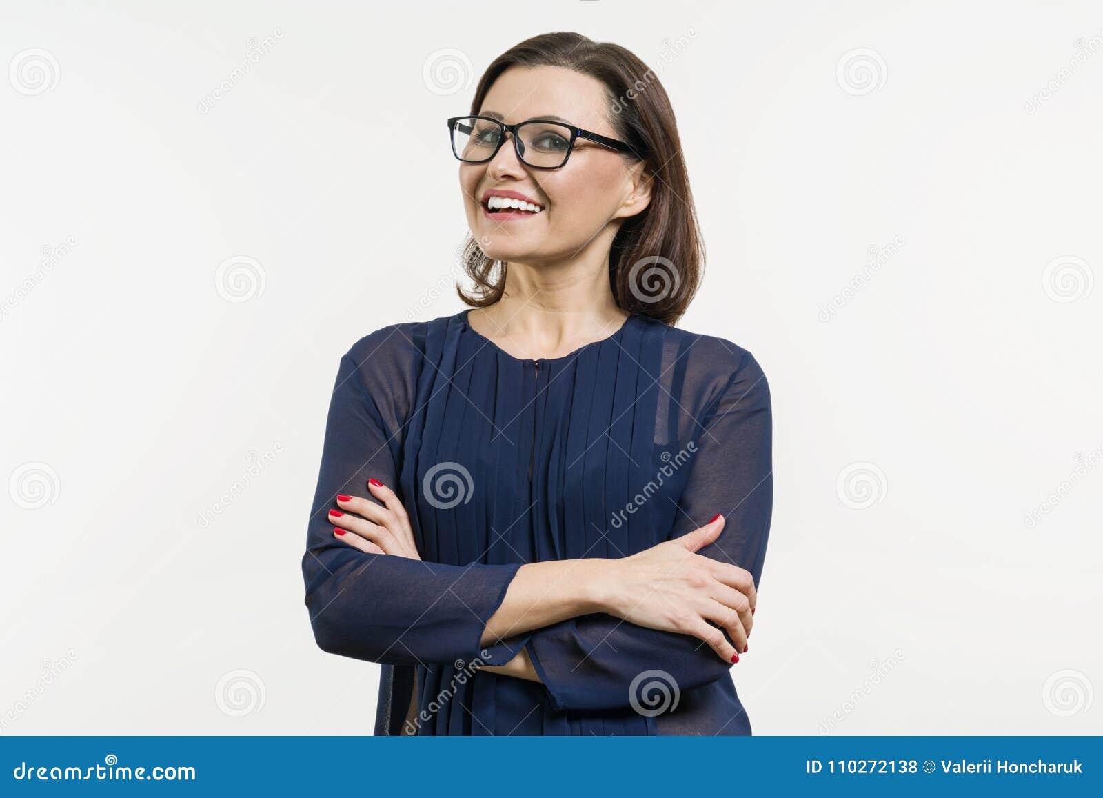 Mulher de negócio positiva da Idade Média que levanta sobre o branco com os braços cruzados
