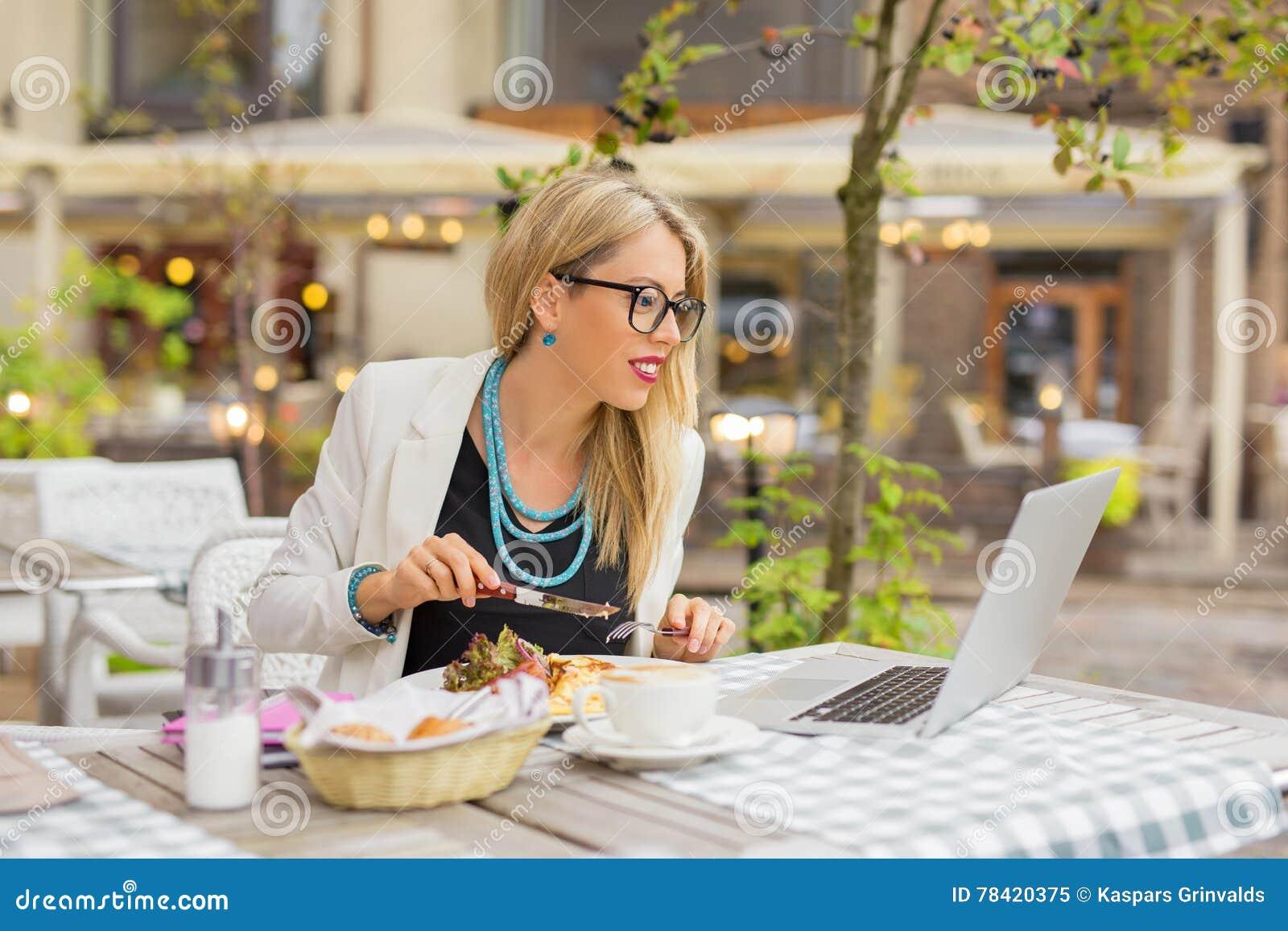 Mulher de negócio que come o almoço e que trabalha no portátil
