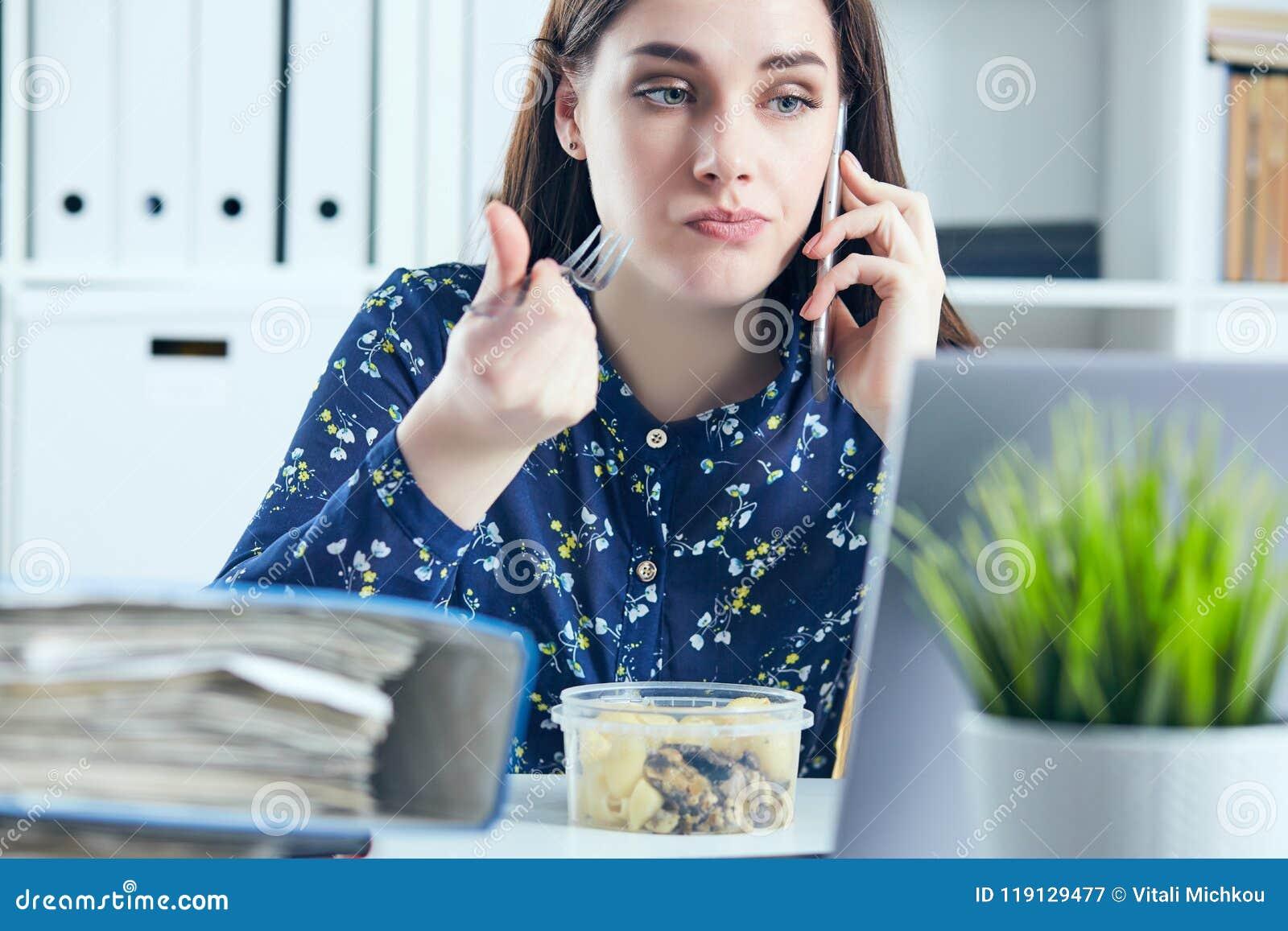 Mulher de negócio que come o almoço em seu local de trabalho que olha a tela do portátil Dobradores com originais no primeiro pla