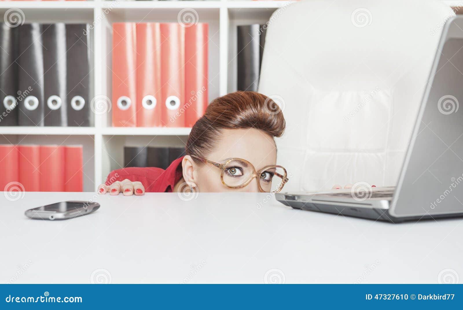 Mulher de negócio que esconde atrás da tabela e receosa