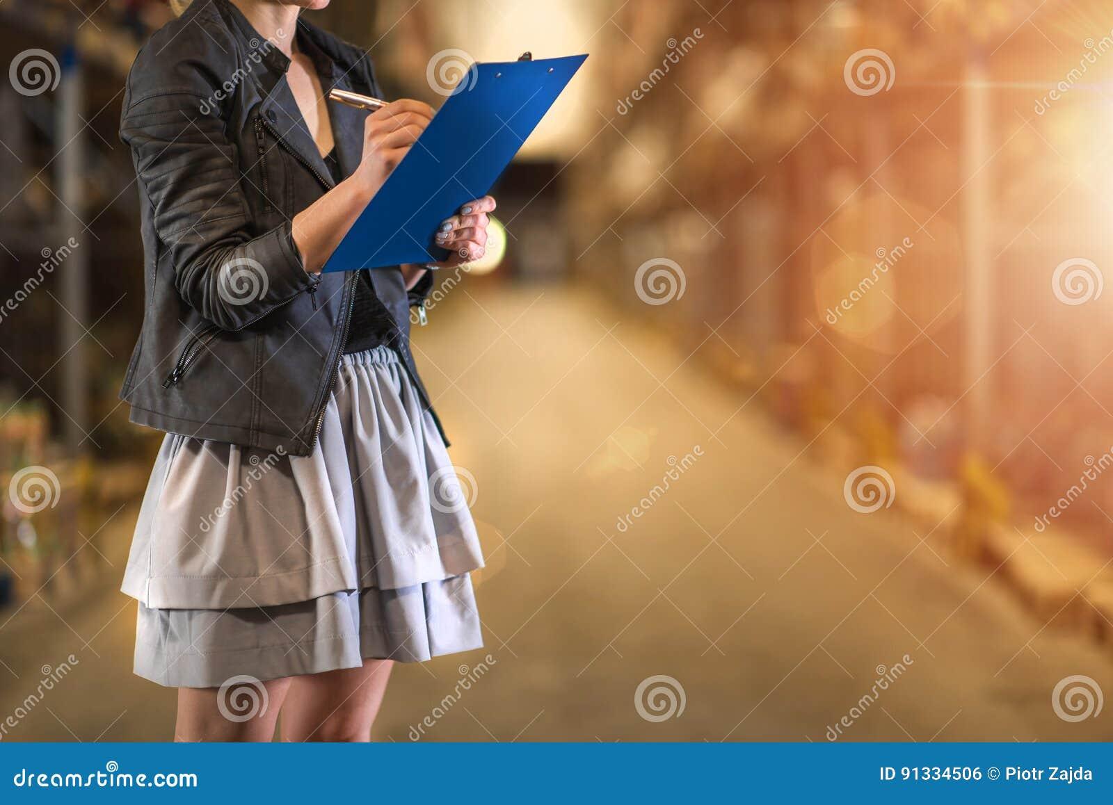 Mulher de negócio que olha acima detalhes da ordem em sua prancheta