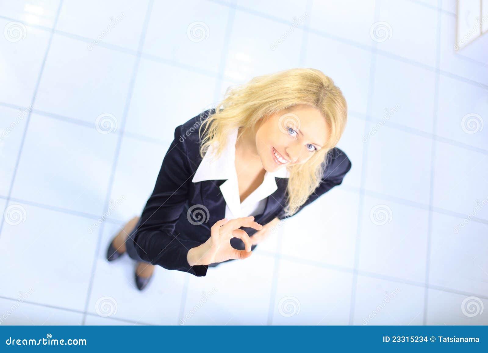 Mulher de negócio que sorri sobre o fundo branco