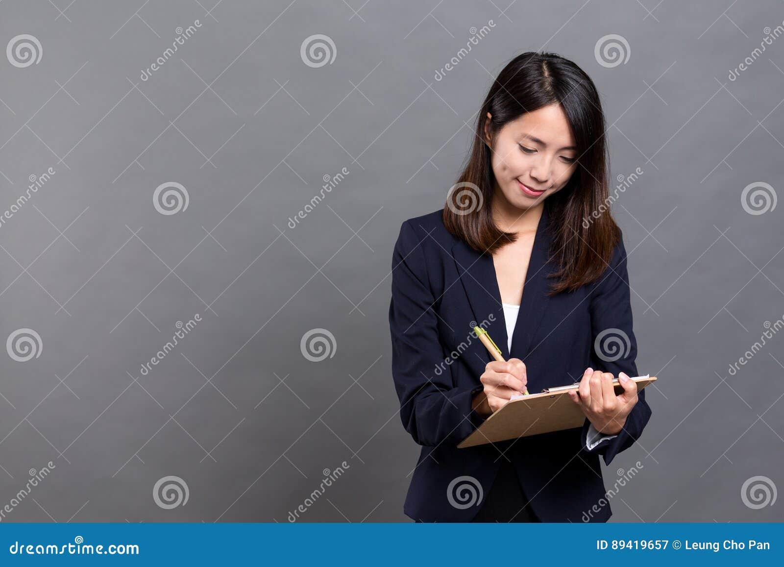 Mulher de negócio que toma a nota na prancheta