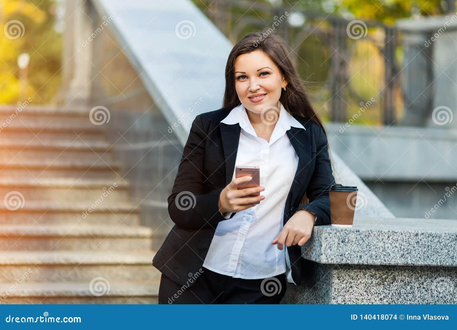 Mulher de negócio que usa o telefone ao andar exterior