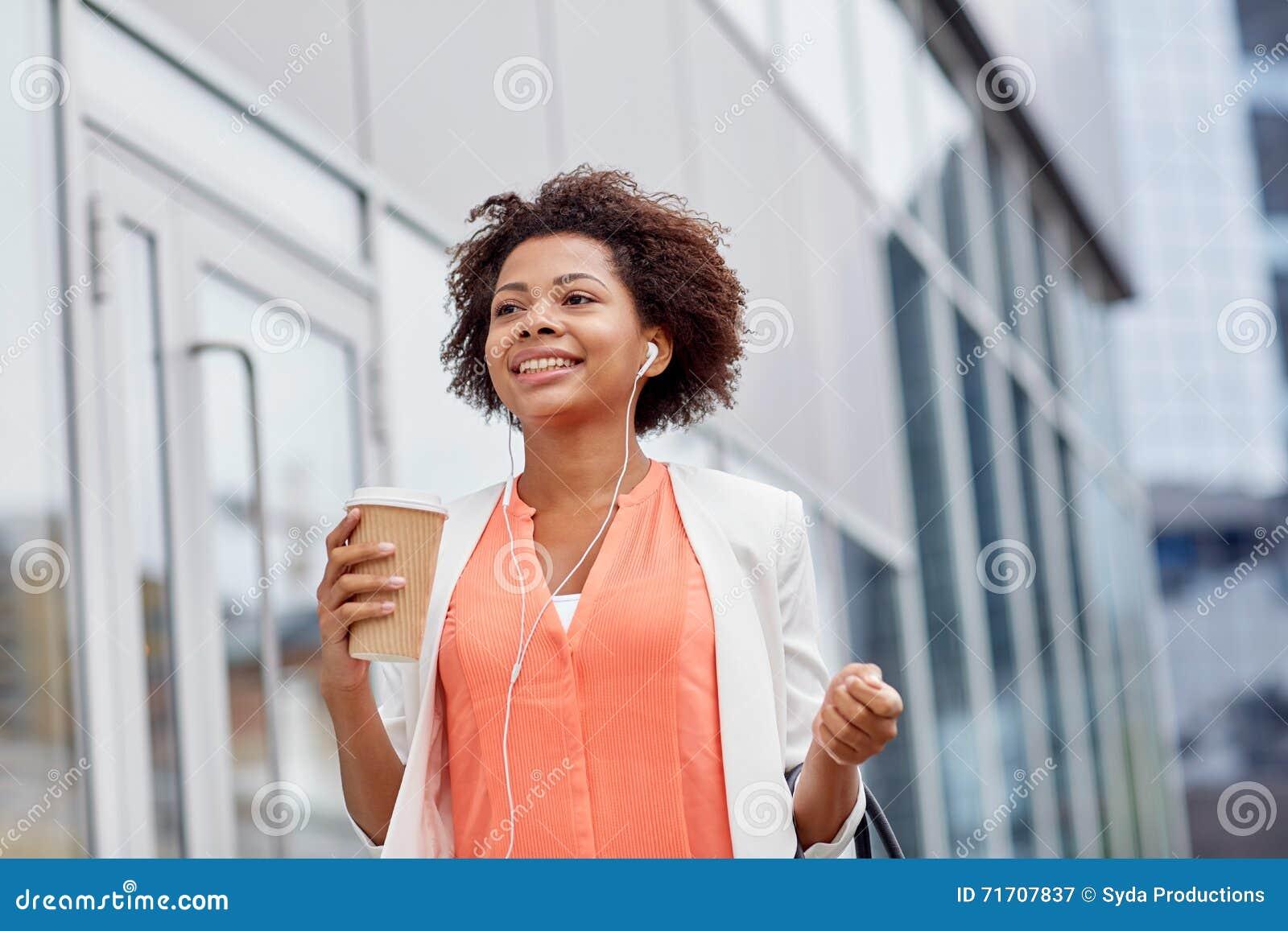 Mulher de negócios africana feliz com café na cidade