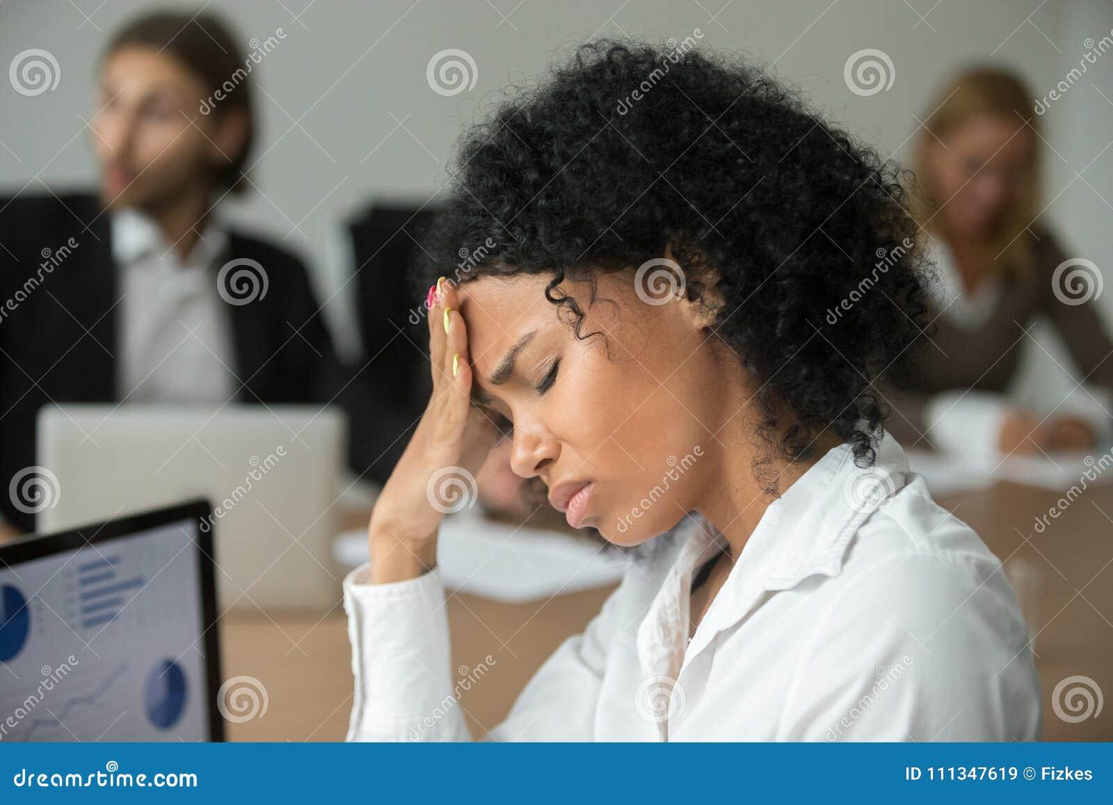 Mulher de negócios africana que sente o sofrimento indisposto da dor de cabeça em