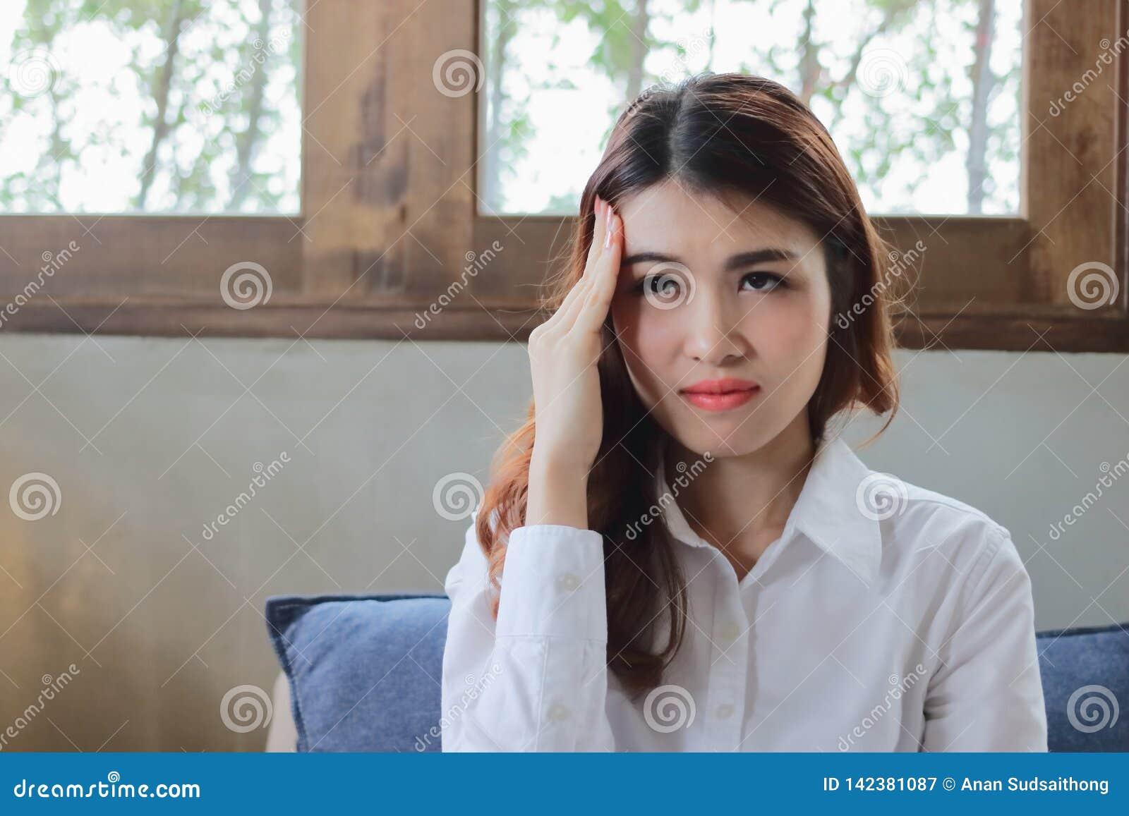 Mulher de negócios asiática nova deprimida esgotada com mão na testa que sente cansado e neutralização com seu trabalho Frustrado