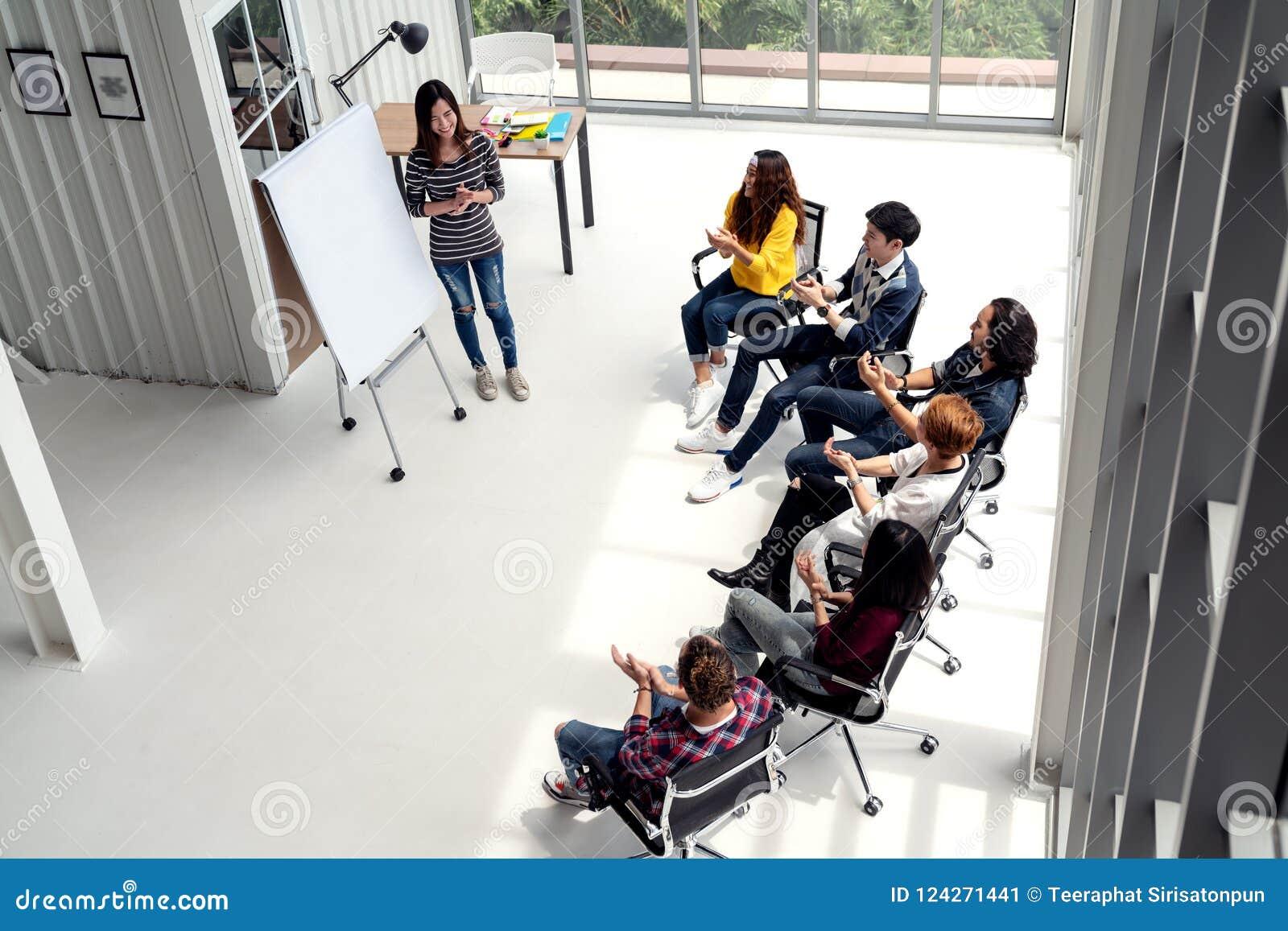 A mulher de negócios asiática nova explica a ideia ao grupo de equipe diversa criativa no escritório moderno