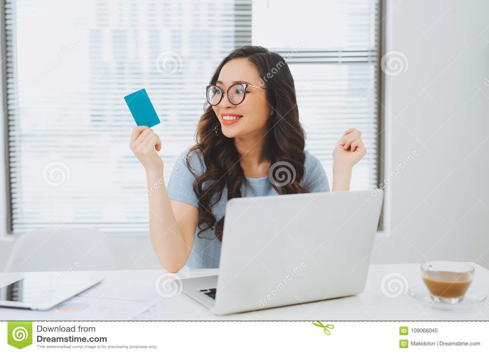 Mulher de negócios asiática nova que usa o cartão de crédito para o pagamento em linha