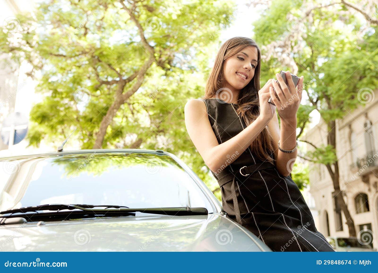 Mulher de negócios que inclina-se no carro com smartphone.
