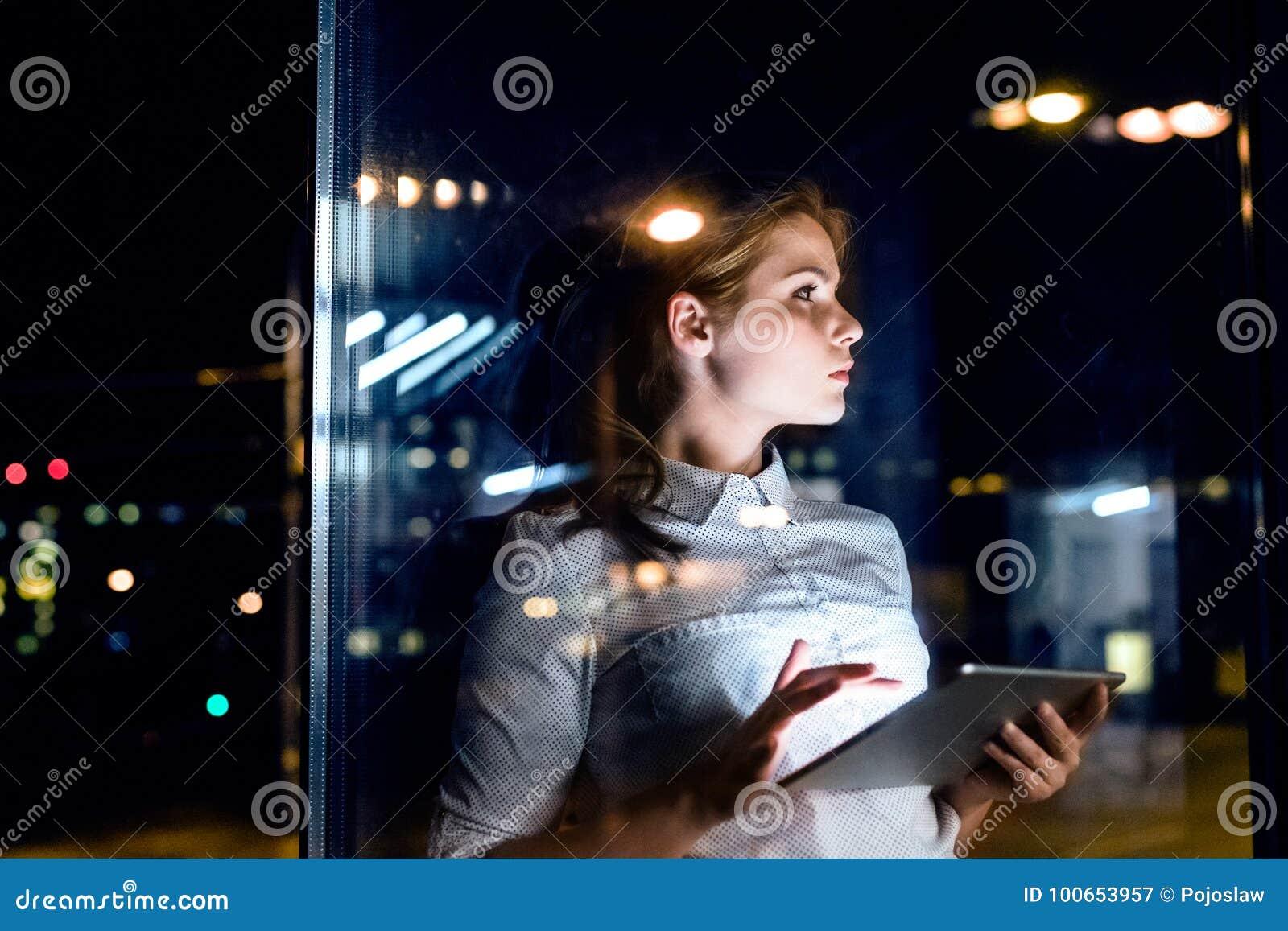 Mulher de negócios com a tabuleta que trabalha tarde na noite