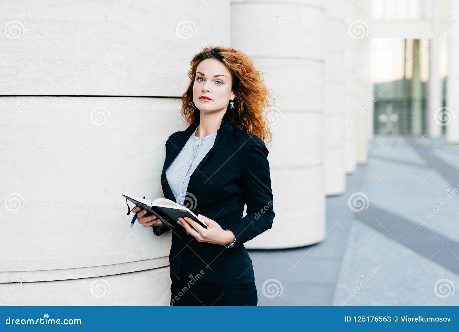 Mulher de negócios consideravelmente nova que veste o revestimento preto, a saia e a blusa branca, guardando seu livro de bolso c