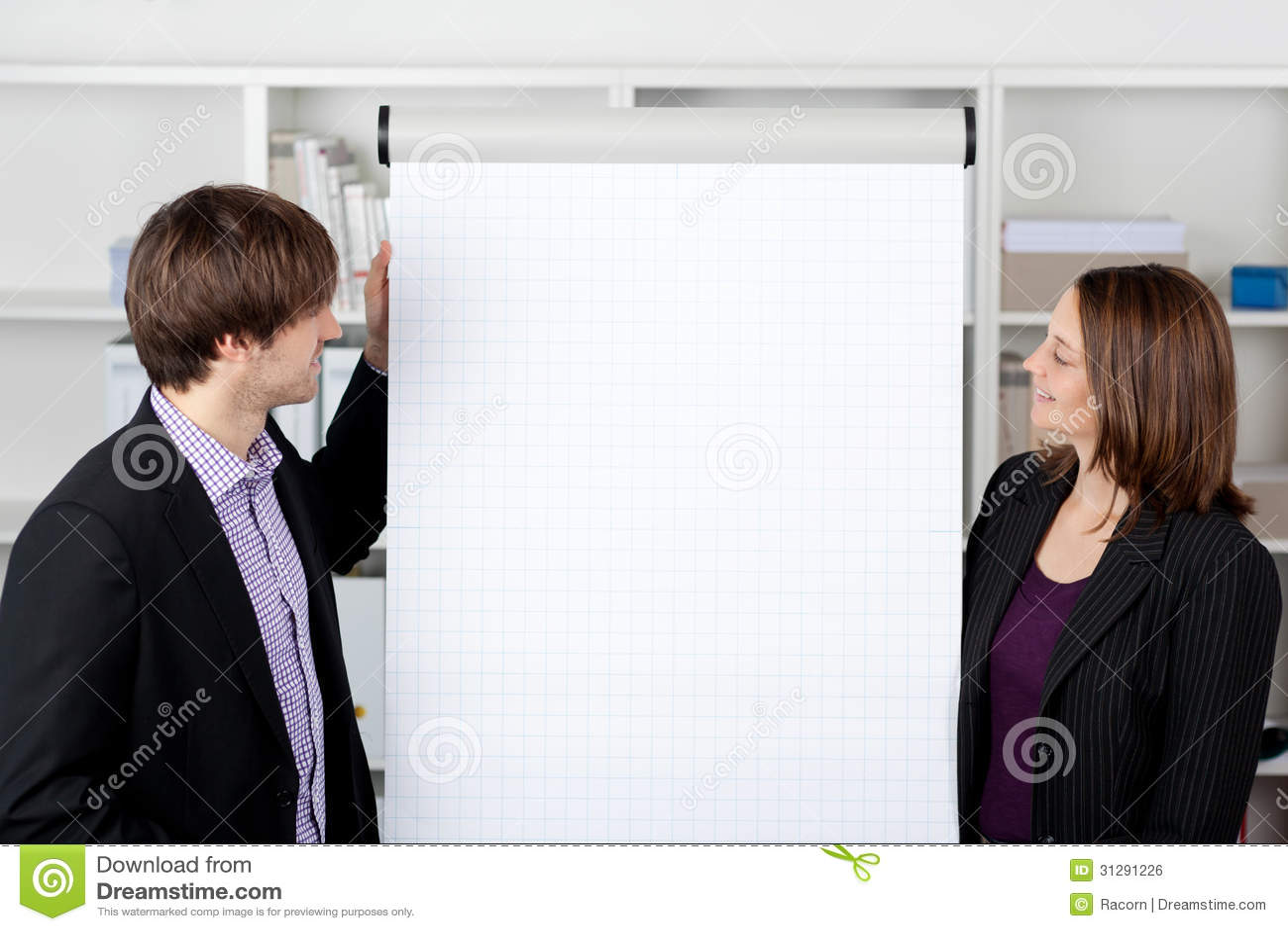 Mulher de negócios With Coworker Looking em Flip Chart