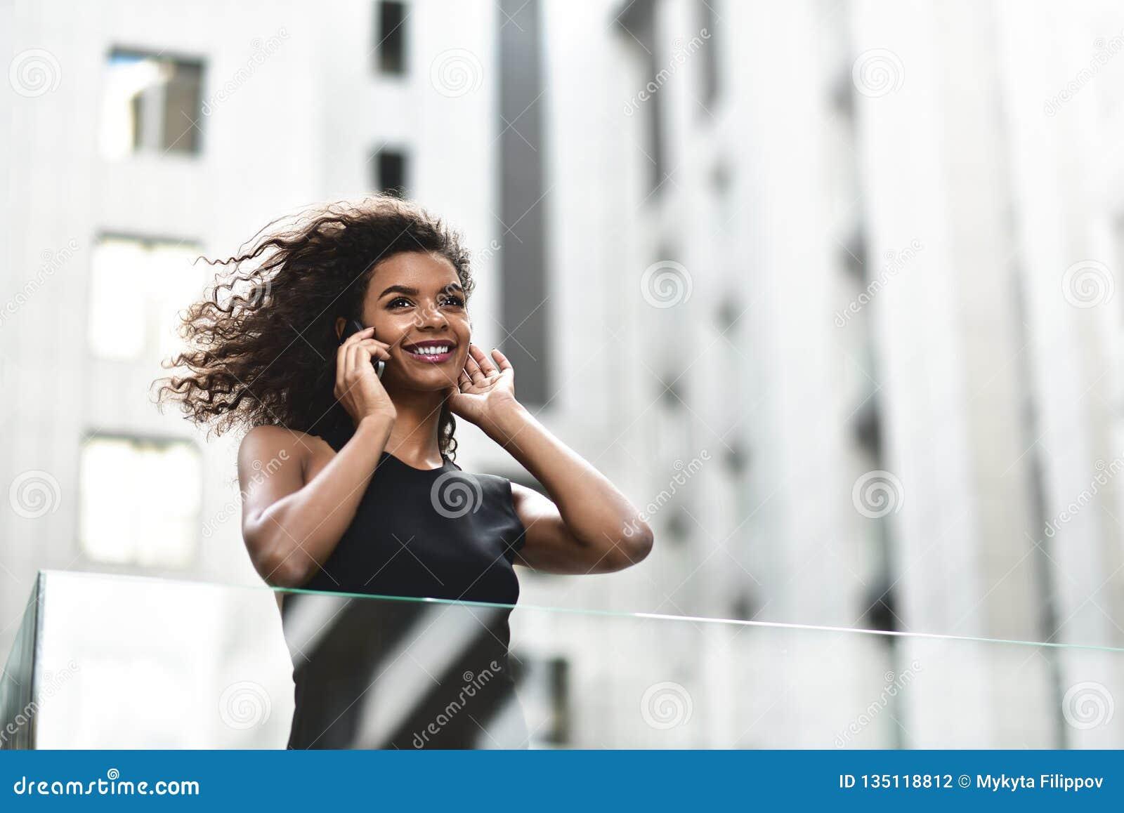A mulher de negócios da raça consideravelmente misturada fala pelo telefone na cidade