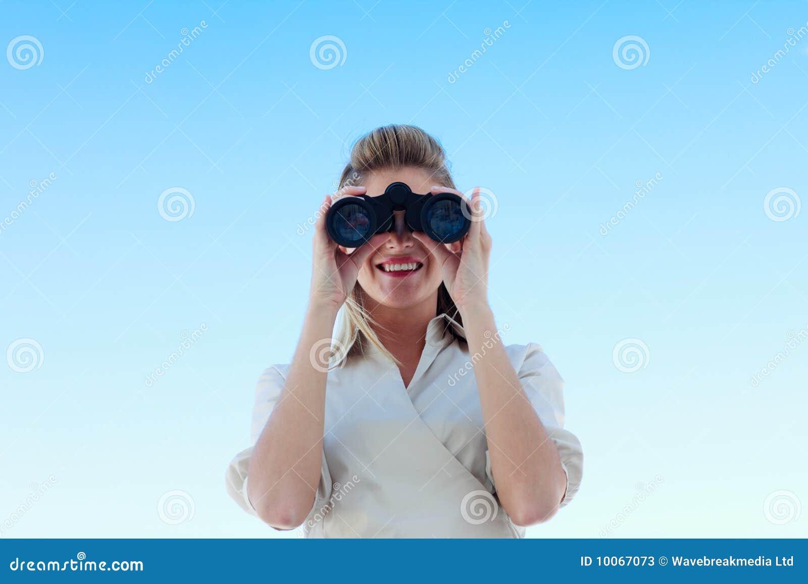 Mulher de negócios de sorriso que olha através dos binóculos