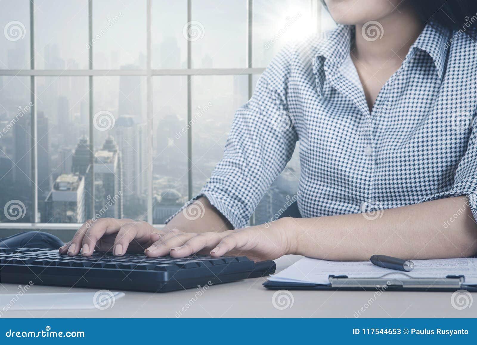 Mulher de negócios desconhecida que trabalha pela janela