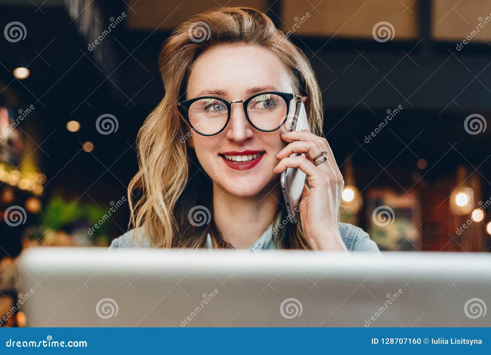 Mulher de negócios do retrato nos vidros que sentam-se no café na frente do portátil, falando no telefone O blogger da menina com
