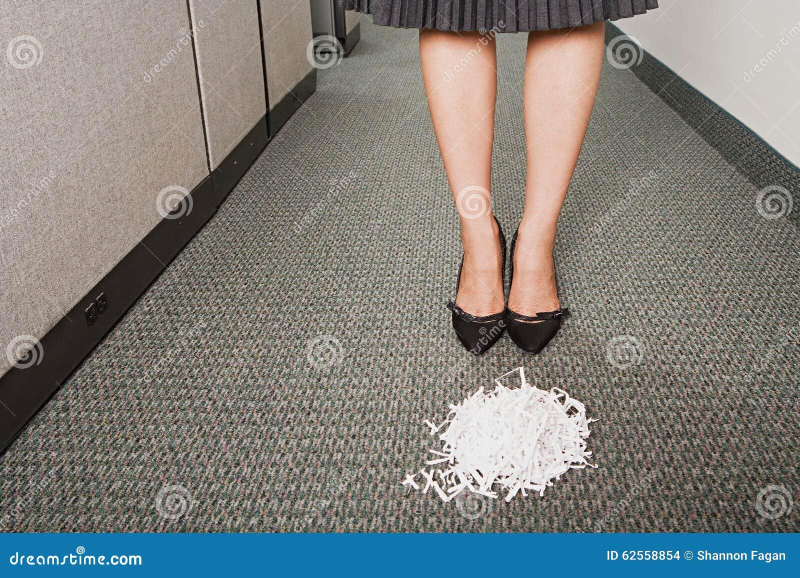 Mulher de negócios estada na frente da pilha dos shreddings de papel