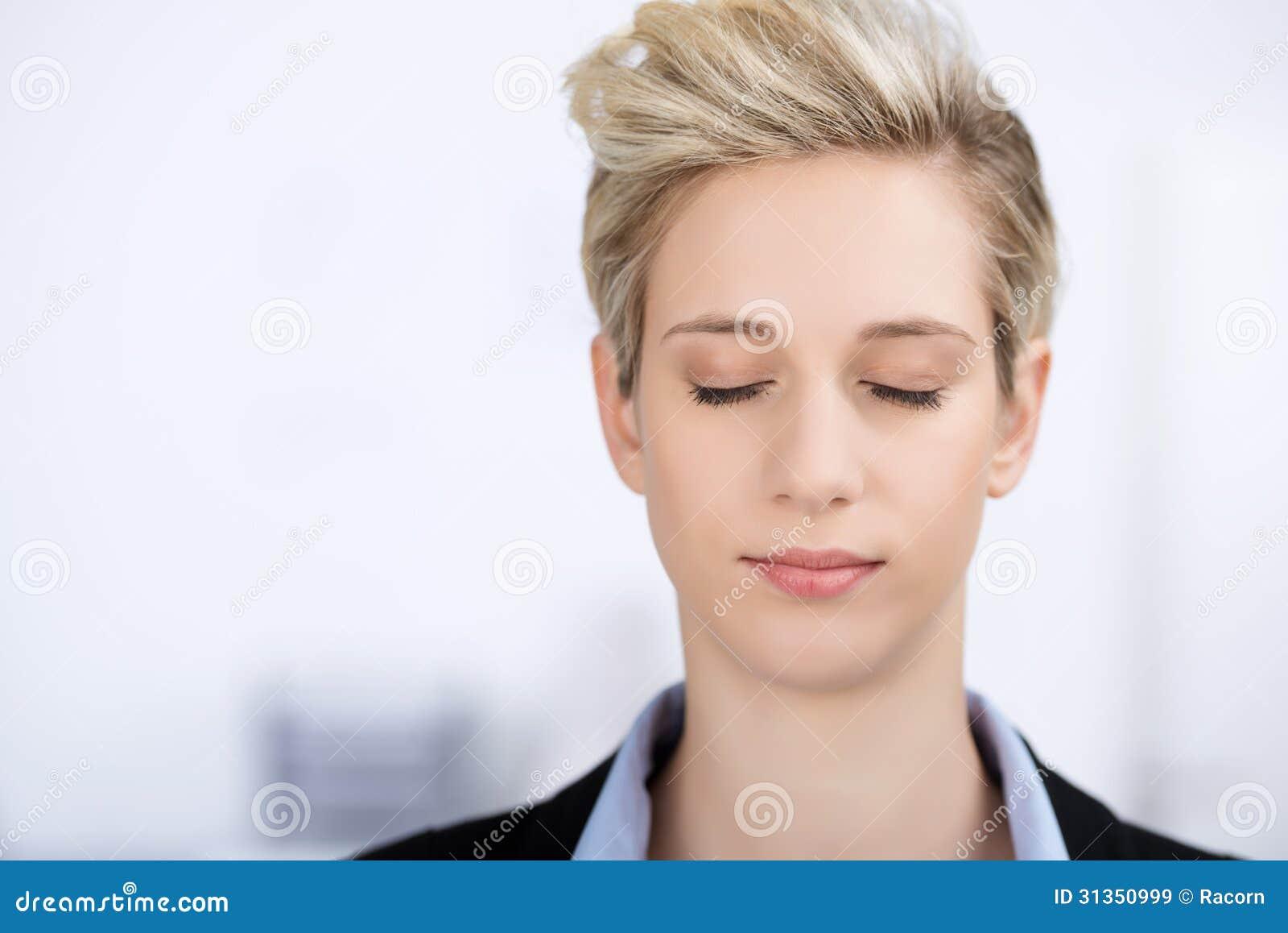 Mulher de negócios With Eyes Closed no escritório