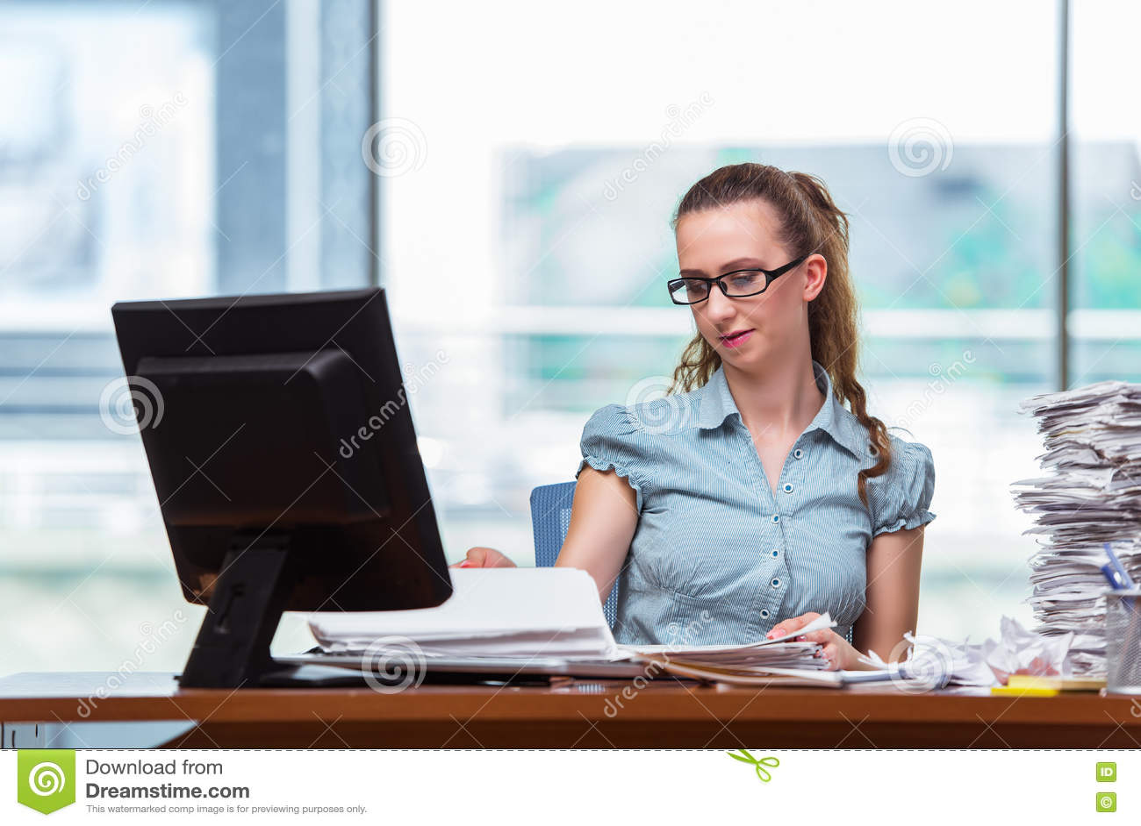 A mulher de negócios forçada com a pilha de papéis