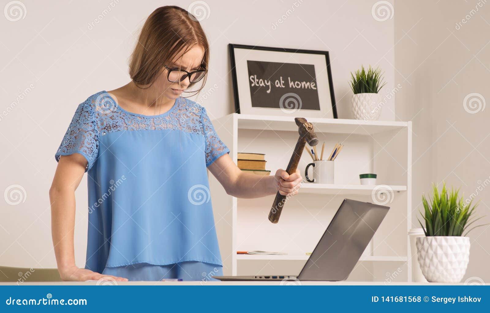 A mulher de negócios irritada foi louca com martelo e portátil