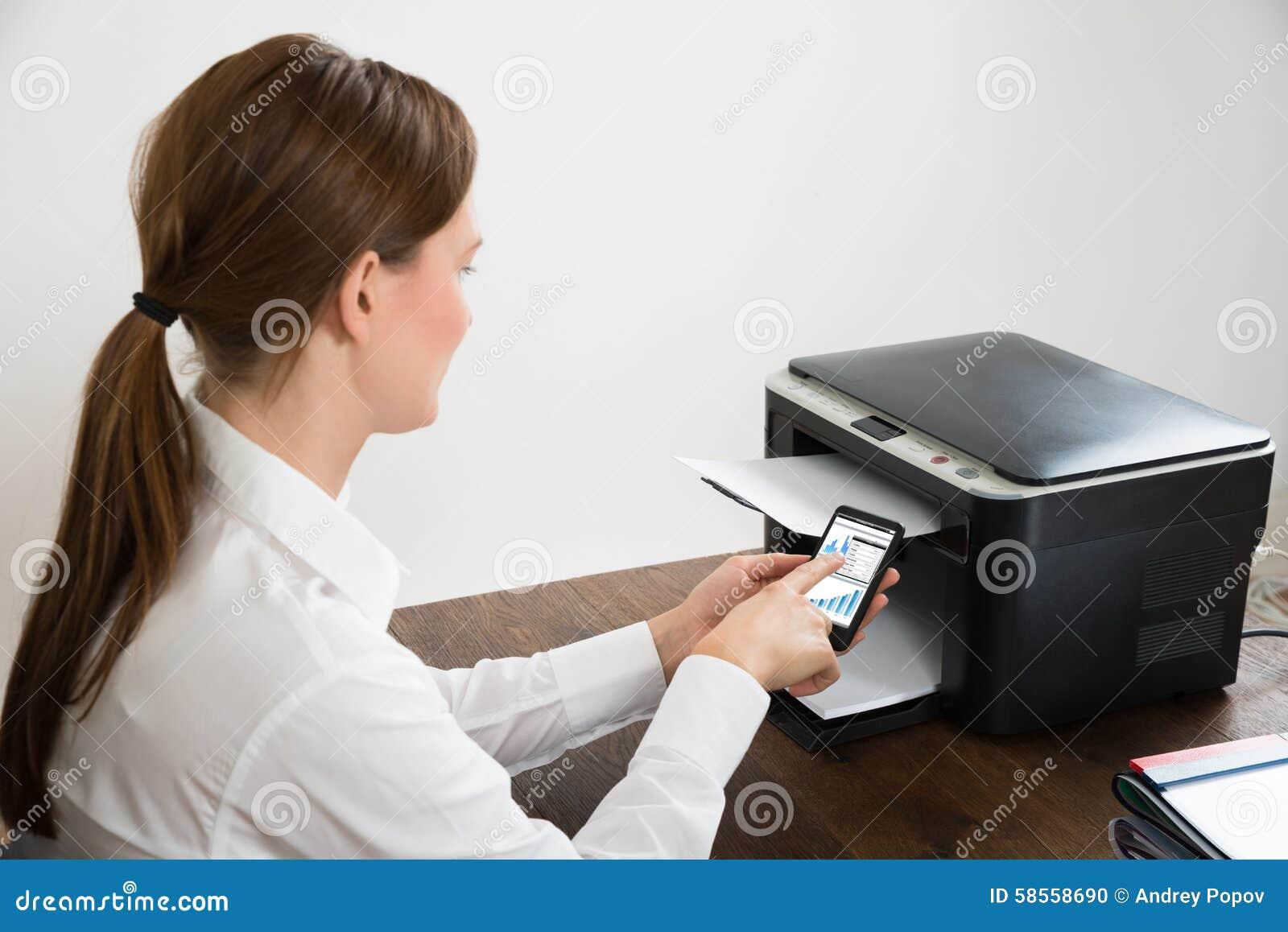 Mulher de negócios With Mobile Phone conectado à impressora