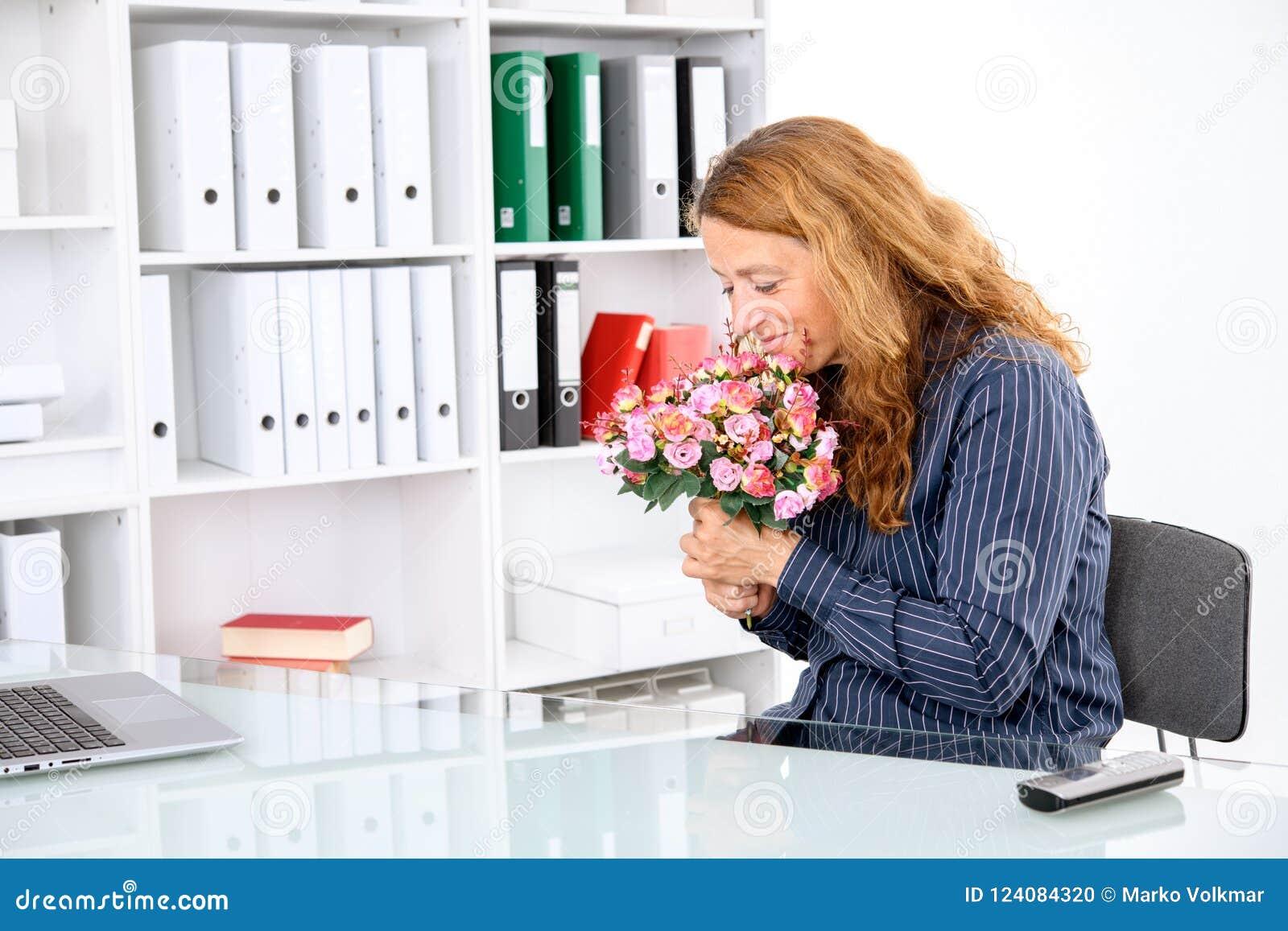 Mulher de negócios no escritório com o ramalhete grande das flores