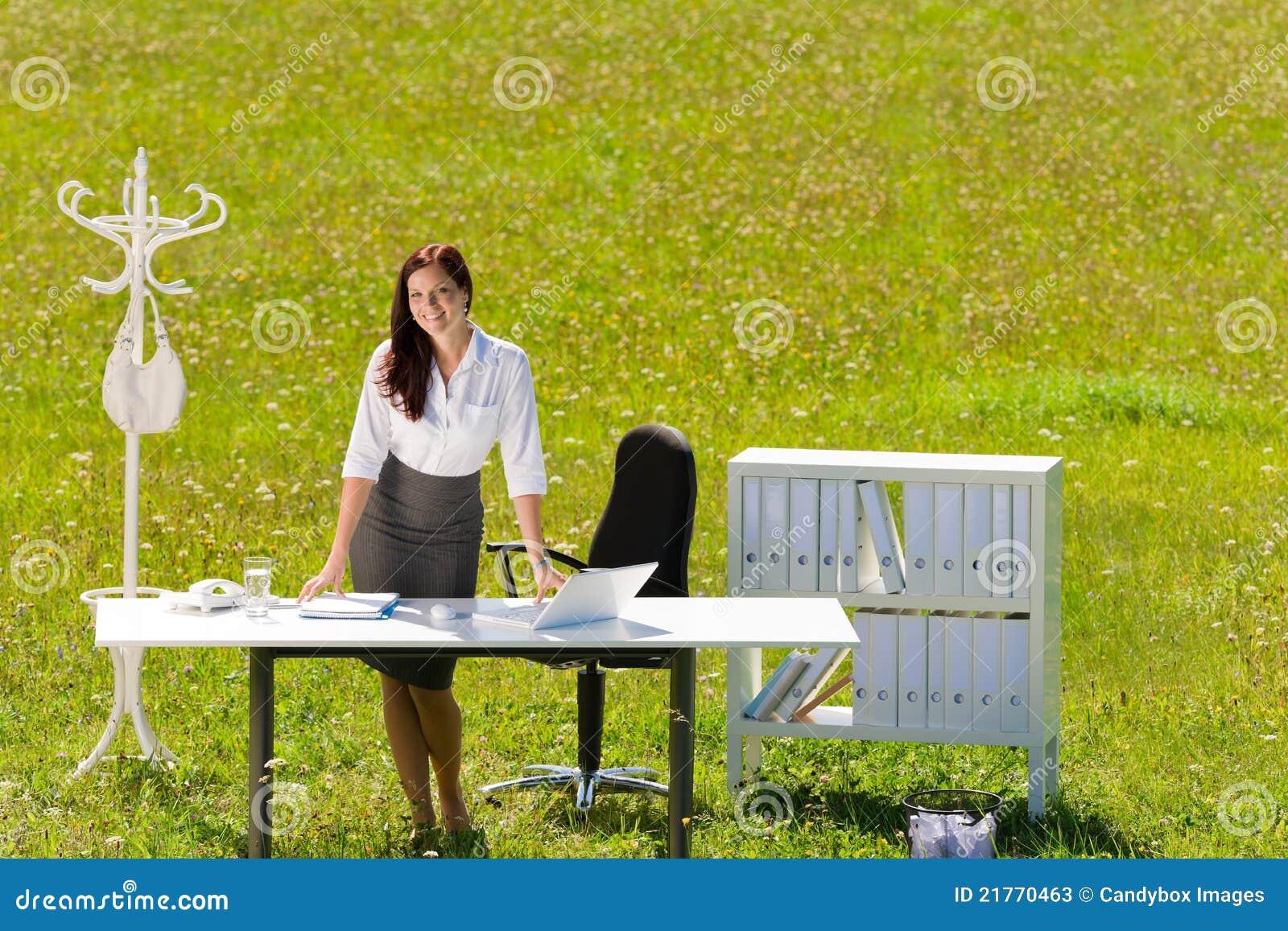Mulher de negócios no sorriso ensolarado do escritório da natureza do prado