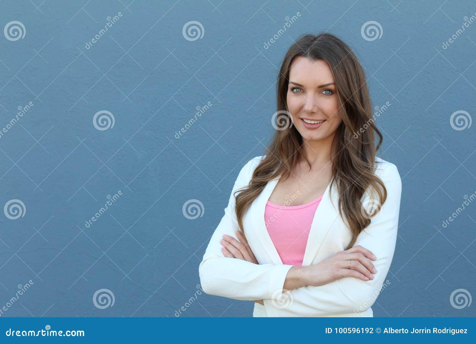 Mulher de negócios nova bonita que sorri com os braços cruzados