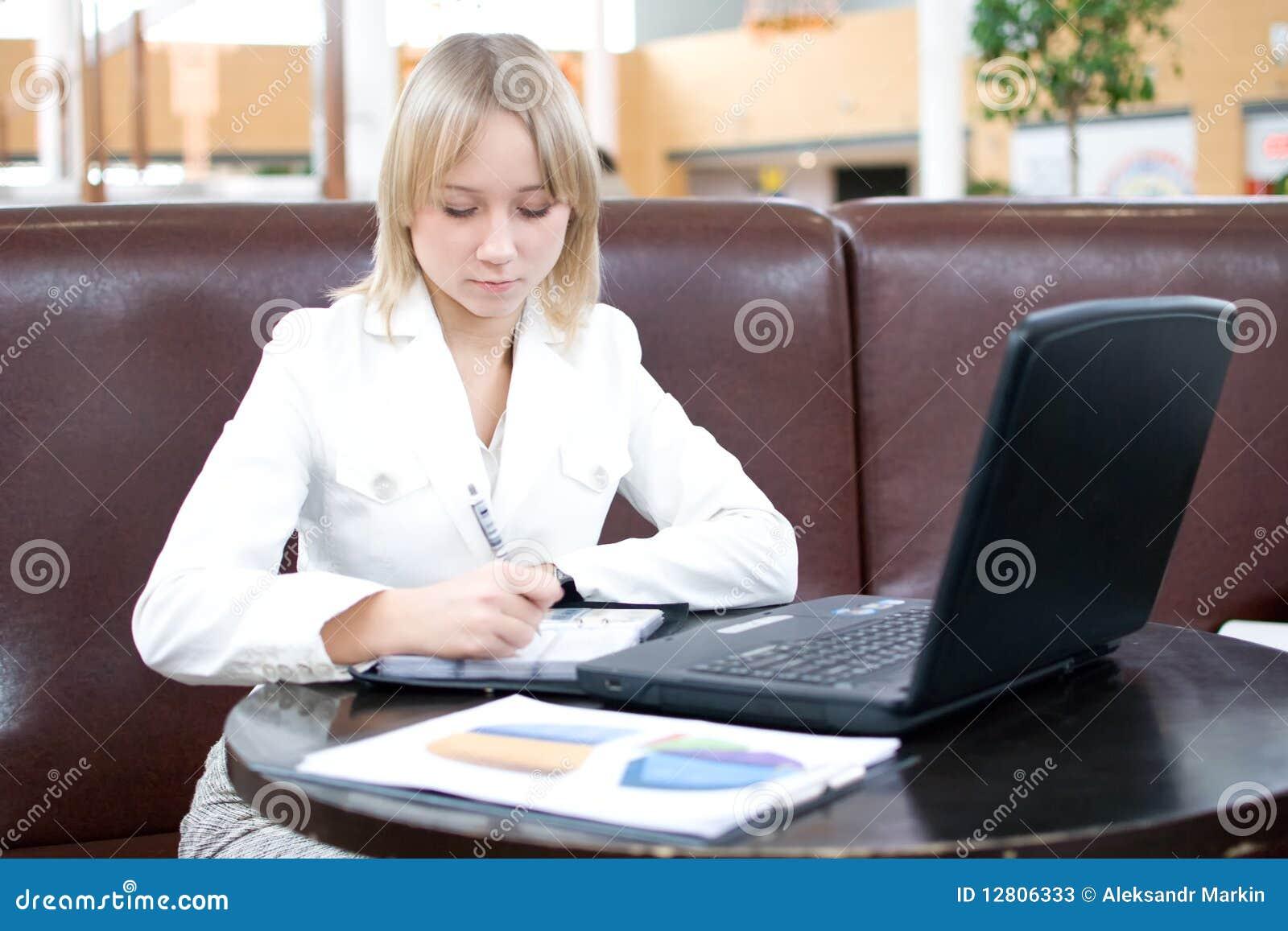 Mulher de negócios nova com o caderno no café