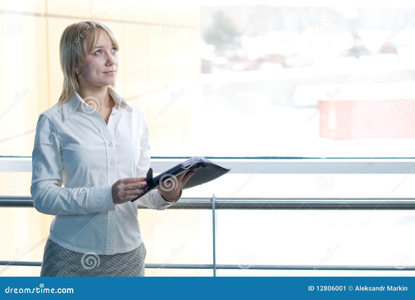 Mulher de negócios nova com o planejador do dia na entrada
