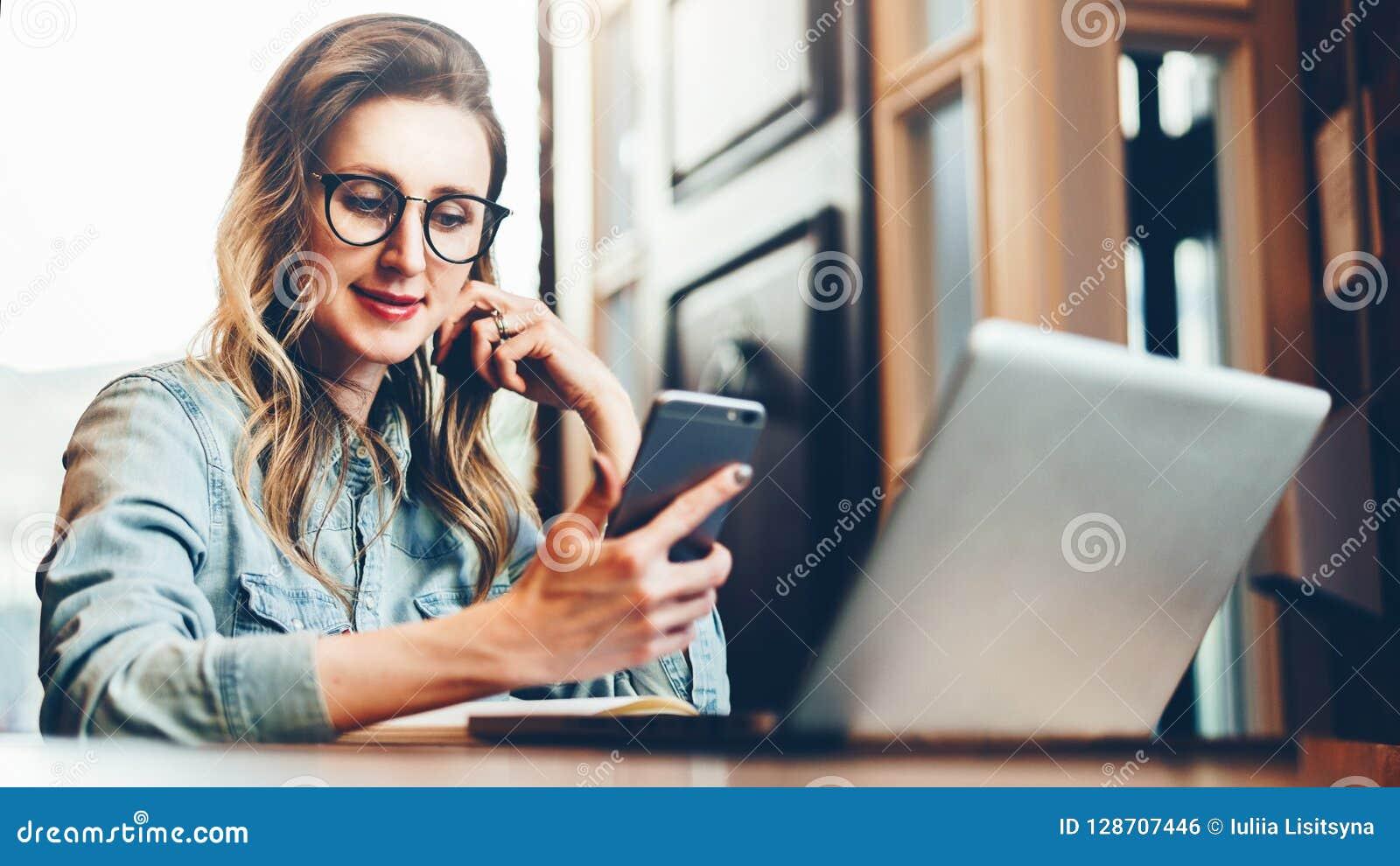 A mulher de negócios nova está sentando-se na cafetaria na tabela na frente do computador e do caderno, usando o smartphone Media