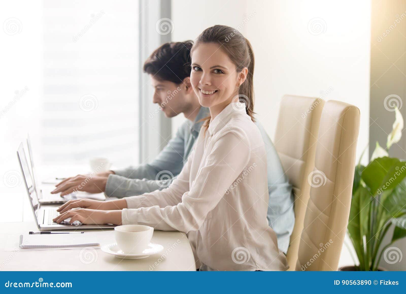 Mulher de negócios nova feliz que olha a câmera, trabalhando com homem c