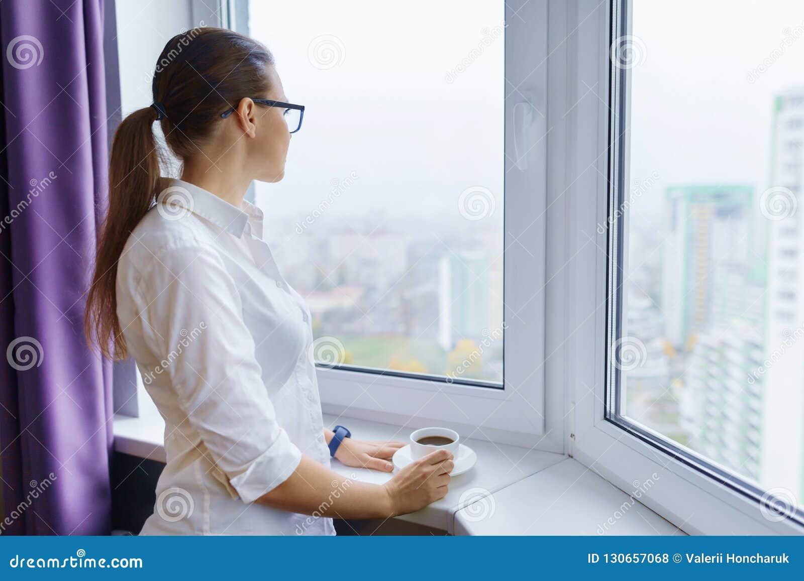 A mulher de negócios nova nos vidros com uma xícara de café perto da janela, mulher moreno olha para fora o sorriso da janela
