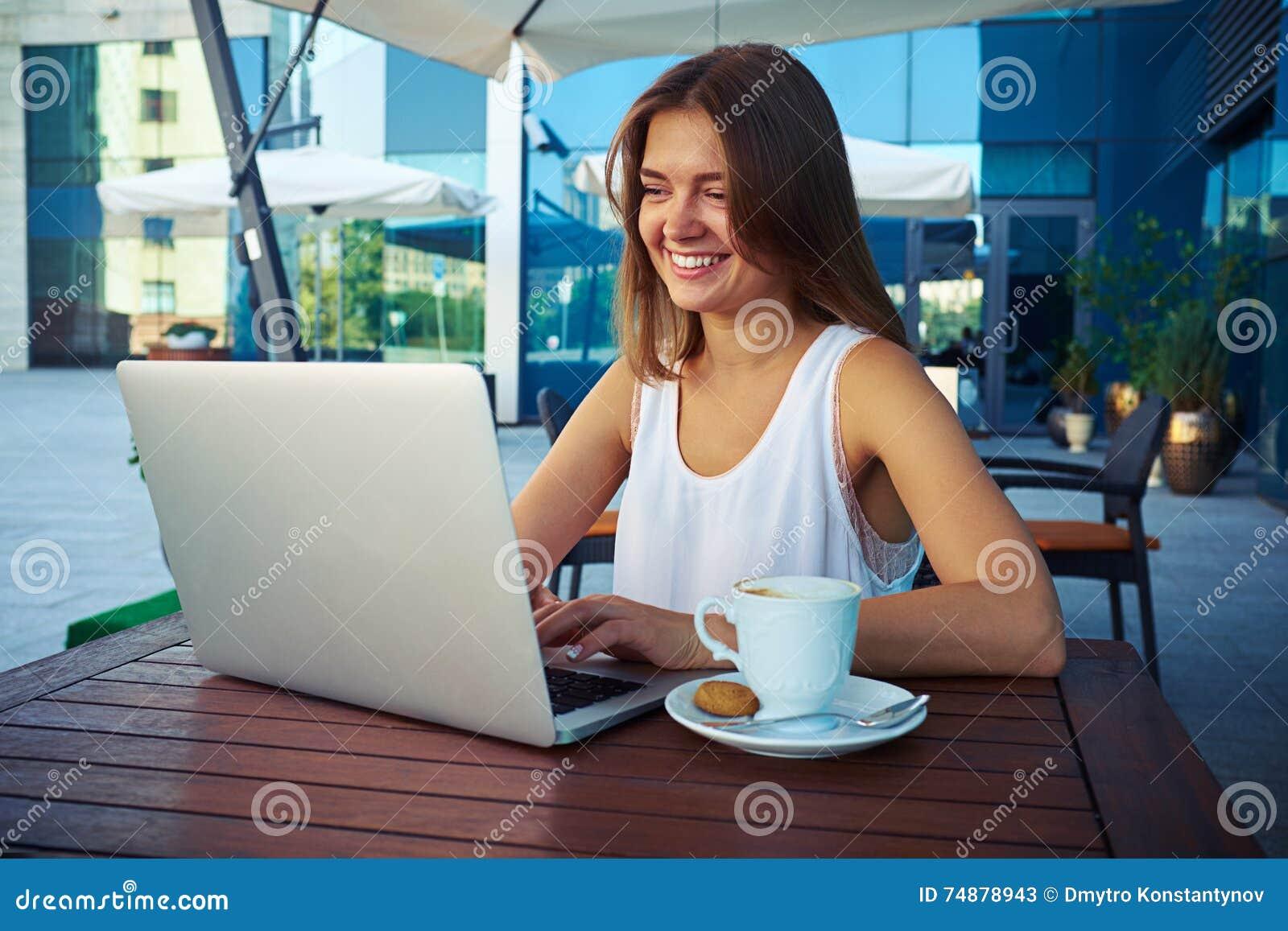 Mulher de negócios nova que senta-se no café exterior com um copo do coffe