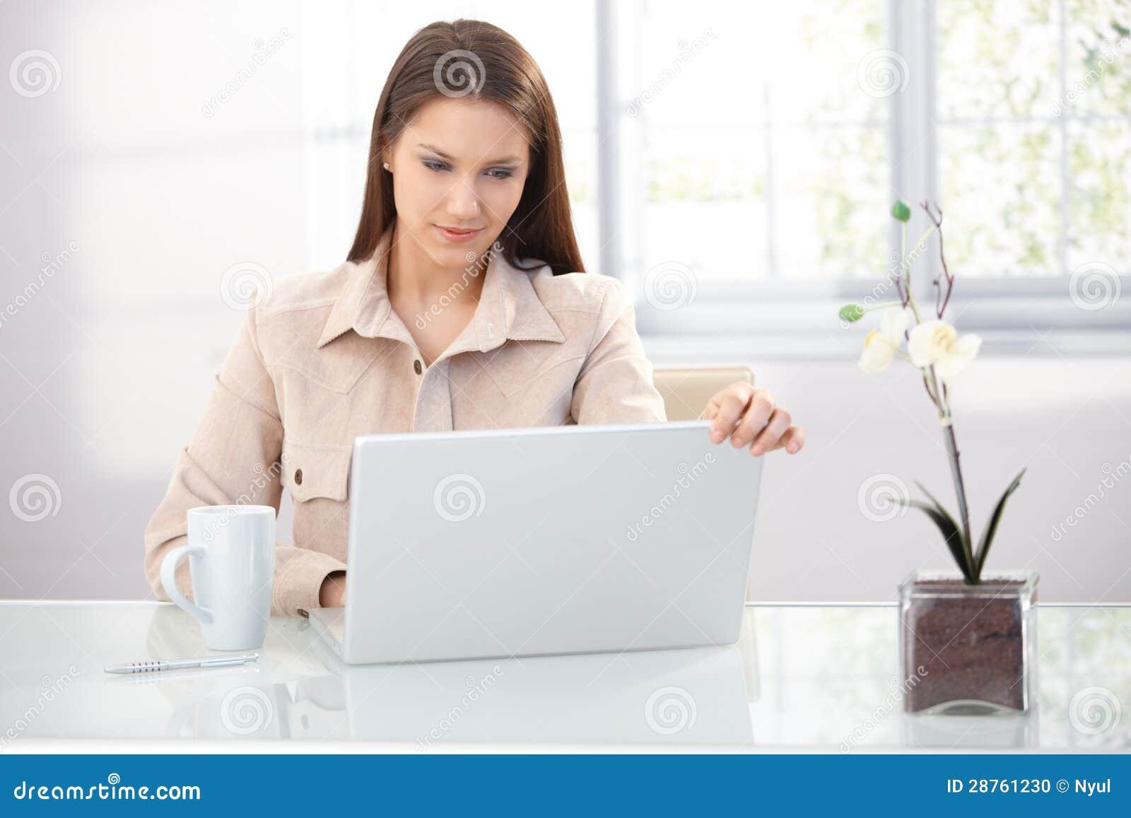 Mulher de negócios nova que trabalha em casa