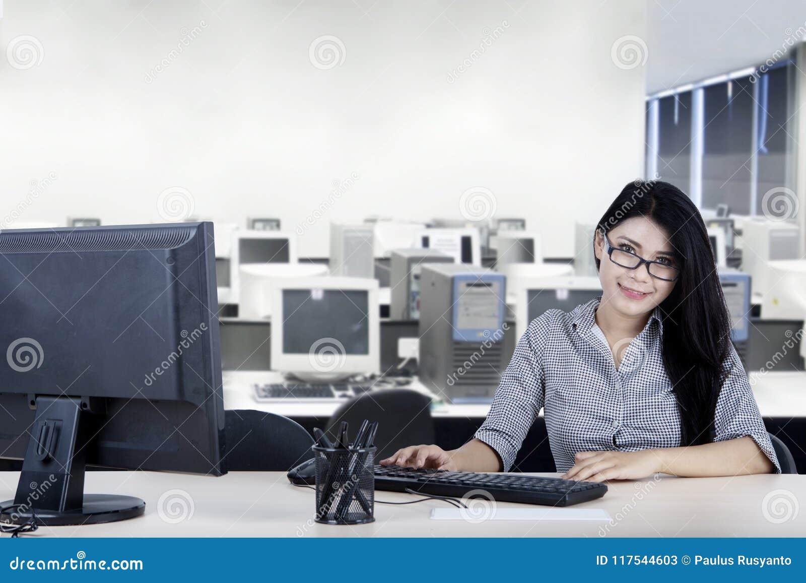 Mulher de negócios nova de sorriso que trabalha no escritório
