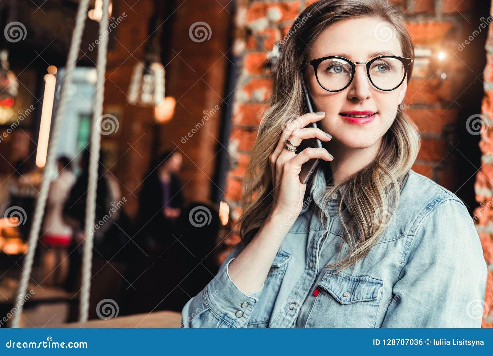 A mulher de negócios nova tem conversações telefônicas Blogger alegre da menina nos vidros na moda que sentam-se no café, falando