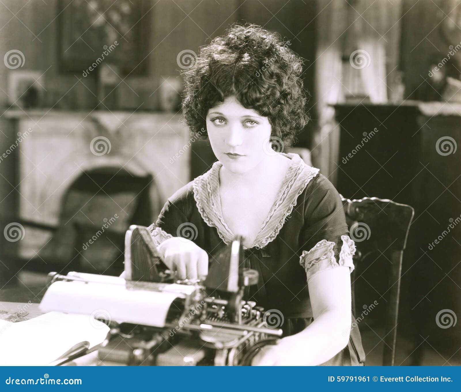 Mulher de negócios pensativa com a máquina de escrever na mesa no escritório