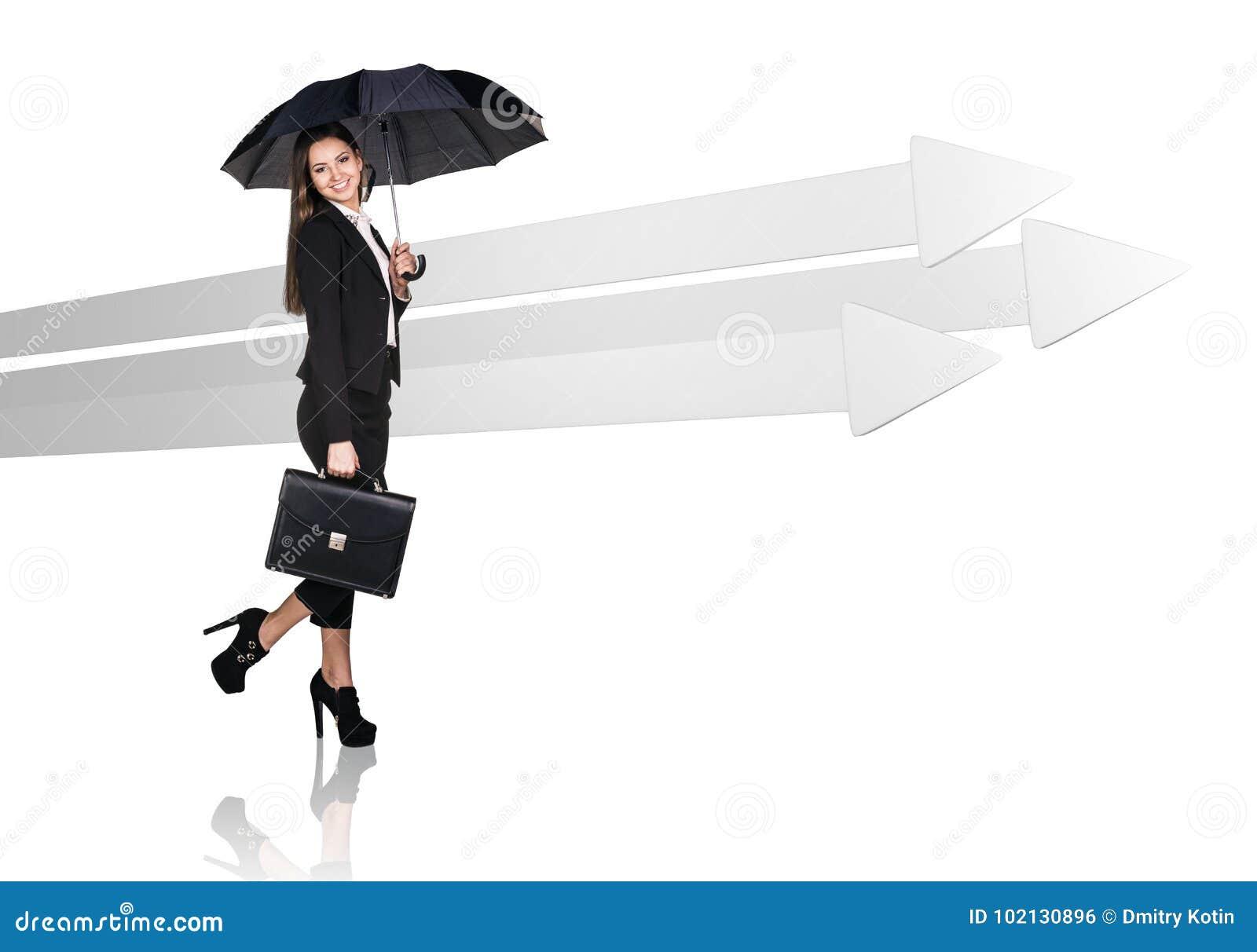 Mulher de negócios que anda perto das setas cinzentas grandes