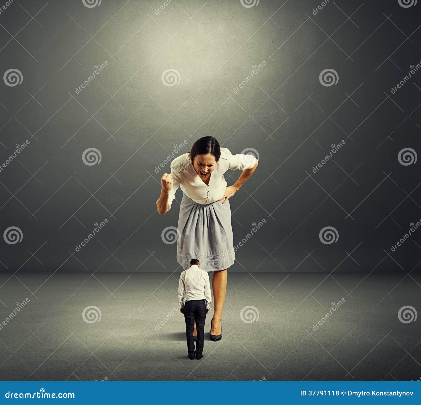 Mulher de negócios que grita no homem pequeno